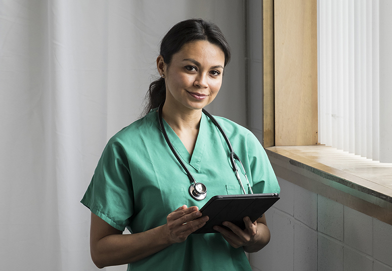 Dedicated nurse health professional with ipad standing next to window